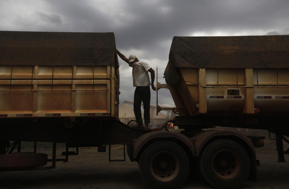 A Brazilian truck driver covers his face to protect himself from dust as he waits to unload his cargo of cereal grain at the rail terminal of America Latina Logistica (ALL), along highway BR-364 in Alto de Araguaia, Mato Grosso state September 24, 2012.  With its rail and river networks underdeveloped, Brazil depends heavily on trucking to move its valuable commodities to port. But traffic bottlenecks, backlogs at port, bureaucracy, and high fuel and labour costs amount to a handicap for the country in its ambitions as a global breadbasket.  Picture taken September 24, 2012. To match Feature BRAZIL-TRANSPORT/GRAINS    REUTERS/Nacho Doce (BRAZIL - Tags: BUSINESS COMMODITIES POLITICS AGRICULTURE TRANSPORT TPX IMAGES OF THE DAY)   ATTENTION EDITORS: PICTURE 28 30 FOR PACKAGE 'TRUCKING BRAZIL'S RICHES' SEARCH 'AUSTERITY' FOR ALL