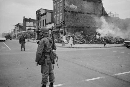 April 8, 1968: A soldier stands guard at 7th and N Street, N.W., Washington, D.C., with the ruins of buildings destroyed during the riots that followed the assassination of Martin Luther King, Jr., in the background. REUTERS/Library of Congress/Handout via Reuters