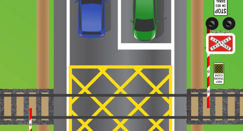 A green car is pictured waiting at a railway crossing.