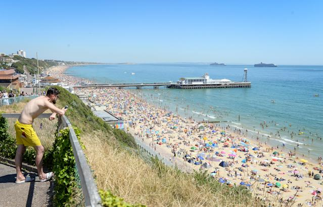 BOURNEMOUTH, ENGLAND - JUNE 25: Visitors enjoy the hot weather on the beach on June 25, 2020 in Bournemouth, United Kingdom. The UK is experiencing a summer heatwave, with temperatures in many parts of the country expected to rise above 30C and weather warnings in place for thunderstorms at the end of the week. (Photo by Finnbarr Webster/Getty Images)