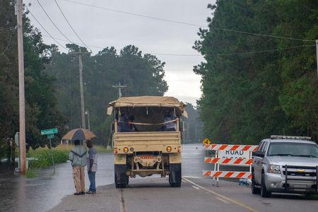 South Carolina National Guard motor transport operators from Bennettsville, S.C., assist local residents evacuating from rising flood waters as a result of Hurricane Florence in Bucksport, South Carolina, U.S. September 24, 2018.  Staff Sgt. Jorge Intriago/U.S. Army National Guard/Handout via REUTERS