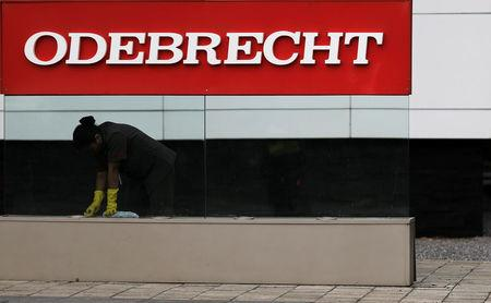 A worker cleans the corporate logo of the Odebrecht SA construction conglomerate at its headquarters in Sao Paulo