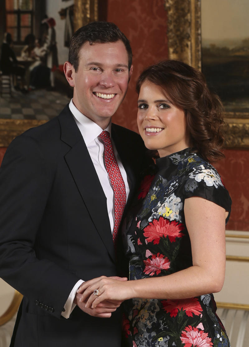 Britain's Princess Eugenie and Jack Brooksbank as they pose for the media in the Picture Gallery at Buckingham Palace after they announced their engagement in London. Britain's Prince Andrew said Friday Feb. 2, 2018 an Oct. 12 wedding date has been set for his younger daughter, Princess Eugenie. (Jonathan Brady/Pool File Photo via AP)