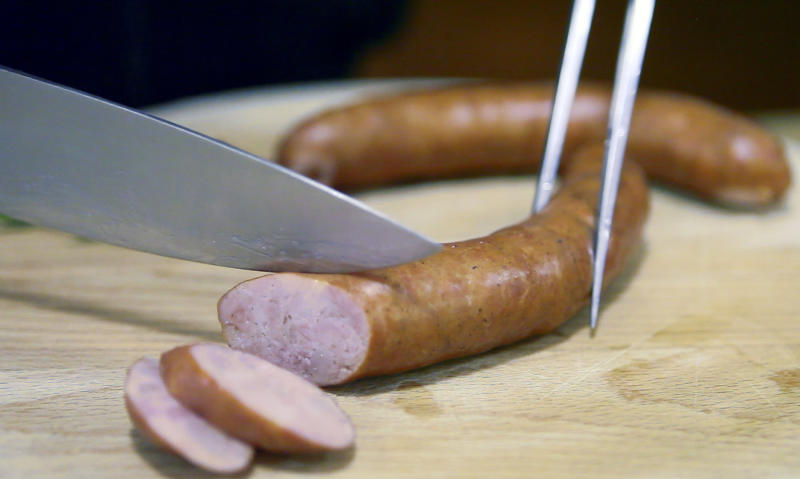 """In this photo taken Thursday, April 19, 2012, a pair of """"Kranjska"""" sausages are cut up in a restaurant in Ljubljana, Slovenia. Slovenia and Austria are gearing up for a diplomatic battle over a delicacy both countries claim their own, a spicy pork sausage. (AP Photo/Darko Bandic)"""