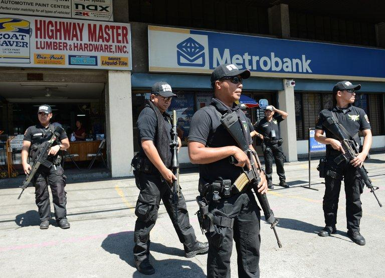 Members of the Pasay City SWAT team patrol in front of a bank in Manila on February 1, 2013