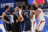 Dallas Mavericks' Luka Doncic, holding ball, and members of the Los Angeles Clippers argue following a play in the first half in Game 3 of an NBA basketball first-round playoff series in Dallas, Friday, May 28, 2021. (AP Photo/Tony Gutierrez)