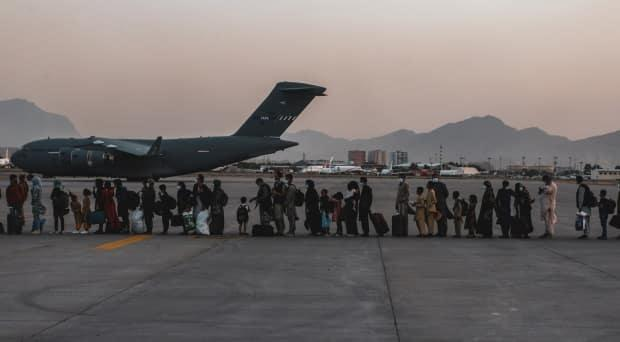 Evacuees wait to board a Boeing C-17 Globemaster III during an evacuation at Hamid Karzai International Airport in Kabul, Afghanistan, on Aug. 23. (U.S. Marine Corps/Reuters - image credit)