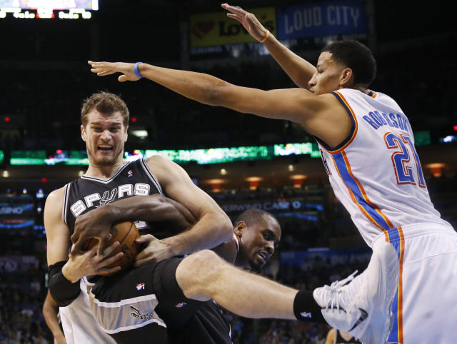 San Antonio Spurs center Tiago Splitter fights for control of the ball with Oklahoma City Thunder forward Serge Ibaka in front of Thunder forward Andre Roberson (21) during the third quarter of an NBA basketball game in Oklahoma City, Thursday, April 3, 2014. Oklahoma City won 106-94. (AP Photo/Sue Ogrocki)