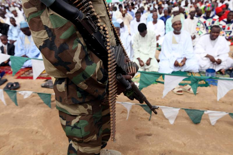 "A Nigerian soldier provides security during Eid al-Fitr prayers at Ramat square in Maiduguri, Nigeria, Thursday, Aug. 8, 2013. Nigerians in the birthplace of an Islamic uprising gripping the northeast celebrated the Muslim holy day of Eid al-Fitr on Thursday with devout prayers and a joyful show of adulation for their king that attracted more than 10,000 people. It was the first durbar in three years in the city of Maiduguri and the joy that it could take place - albeit amid massive security - was heard in the cries of ululating women, screams of delight from children and men chanting ""Long live the king!"" (AP Photo/Sunday Alamba)"