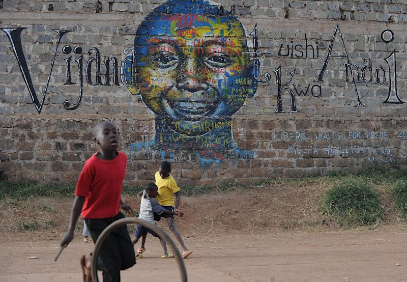 Boys play July 28, 2014 in front of a mural that calls for youth to live in peace in the swahili language in Nairobi's sprawling Kibera slum , a hotspot of deadly ethnic violence following the disputed results of the 2007 general elections (AFP Photo/Tony Karumba)