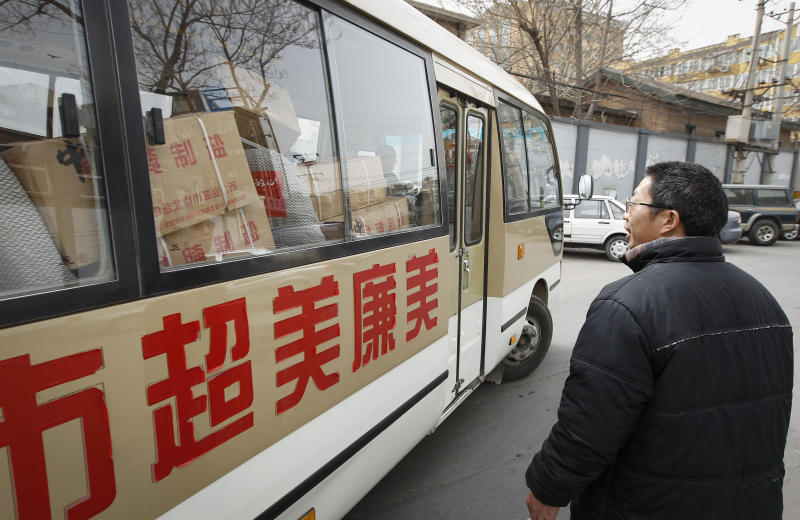 A Chinese looks at a mini bus transporting salt from a distribution center after salt were sold out in Beijing, China, Friday, March 18, 2011. Shoppers in Beijing, Shanghai and other parts of China have stripped supermarket shelves empty of table salt in recent days in the false belief that it either wards off radiation injuries or that the nation's supply would be contaminated by fallout from the crippled Japanese nuclear power plant. (AP Photo/Vincent Thian)