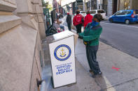 FILE - In this Oct. 14, 2020, file photo, Eva Abodoadji drops off a mail ballot into an official ballot drop box as voters wait in line at City Hall as in-person early voting begins for the general election in Rhode Island in Providence, R.I. As it has for more than 170 years, The Associated Press will count the vote and report the results of presidential, congressional and state elections quickly, accurately and without fear or favor on Nov. 3 and beyond. (AP Photo/David Goldman)