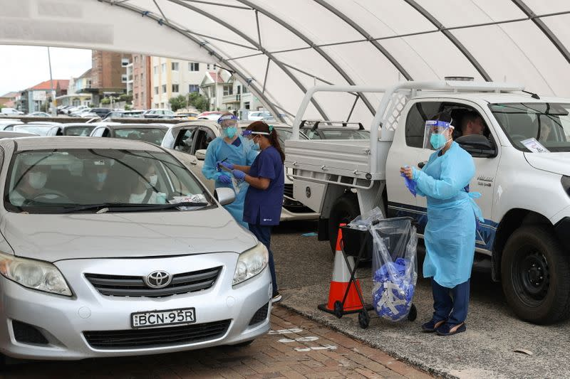 Medical workers administer tests at a drive-through COVID-19 testing centre in Sydney