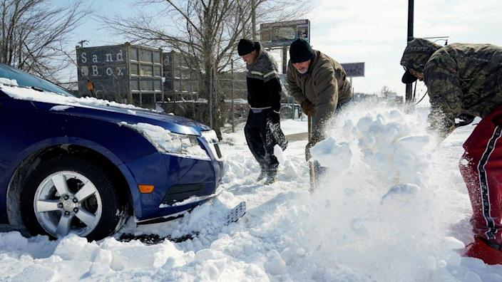 People work to free a car stuck in the snow during record breaking cold weather in Oklahoma City, Oklahoma, U.S., February 15, 2021.