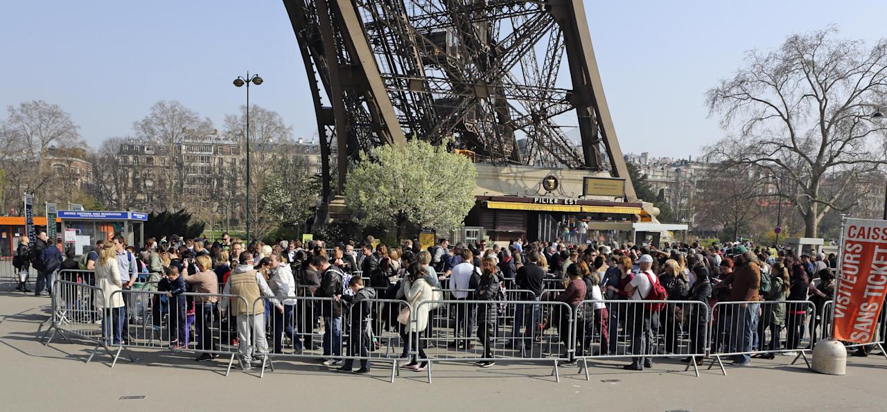 Tourists wait in line at the foot of the Eiffel Tower in Paris, Thursday March 13, 2014. Lines stretch for hours, leaving visitors to bake in the summer or soak in the rain for fear of losing their place. Socialist candidate for Paris mayor Anne Hidalgo wants to create an underground welcome area and rethink how people visit France's most popular monument. (AP Photo/Remy de la Mauviniere)