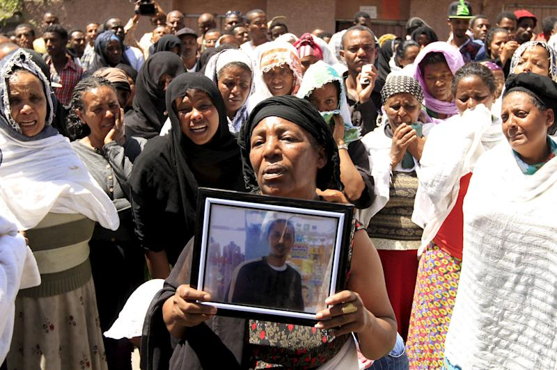 A woman mourns with the framed picture of a man said to be among the 30 Ethiopian victims killed by members of the militant Islamic State in Libya, in the capital Addis Ababa