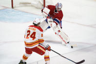 Montreal Canadiens goaltender Jake Allen clears the puck away from Calgary Flames' Brett Ritchie during the third period of an NHL hockey game Friday, April 16, 2021, in Montreal. (Paul Chiasson/The Canadian Press via AP)