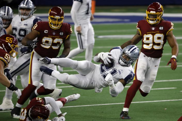 Dallas Cowboys running back Ezekiel Elliott (21) leaps forward on a carry for a first down between Washington Football Team's Cole Holcomb (55), Kamren Curl (31), Jonathan Allen (93) and Chase Young (99) in the second half of an NFL football game in Arlington, Texas, Thursday, Nov. 26, 2020. (AP Photo/Ron Jenkins)