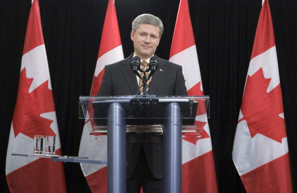 Stephen Harper stands at a podium with Canadian flags behind him.
