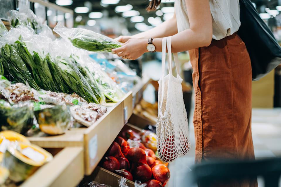 Cropped shot of young Asian woman shopping for fresh organic groceries in supermarket. She is shopping with a cotton mesh eco bag and carries a variety of fruits and vegetables. Zero waste concept