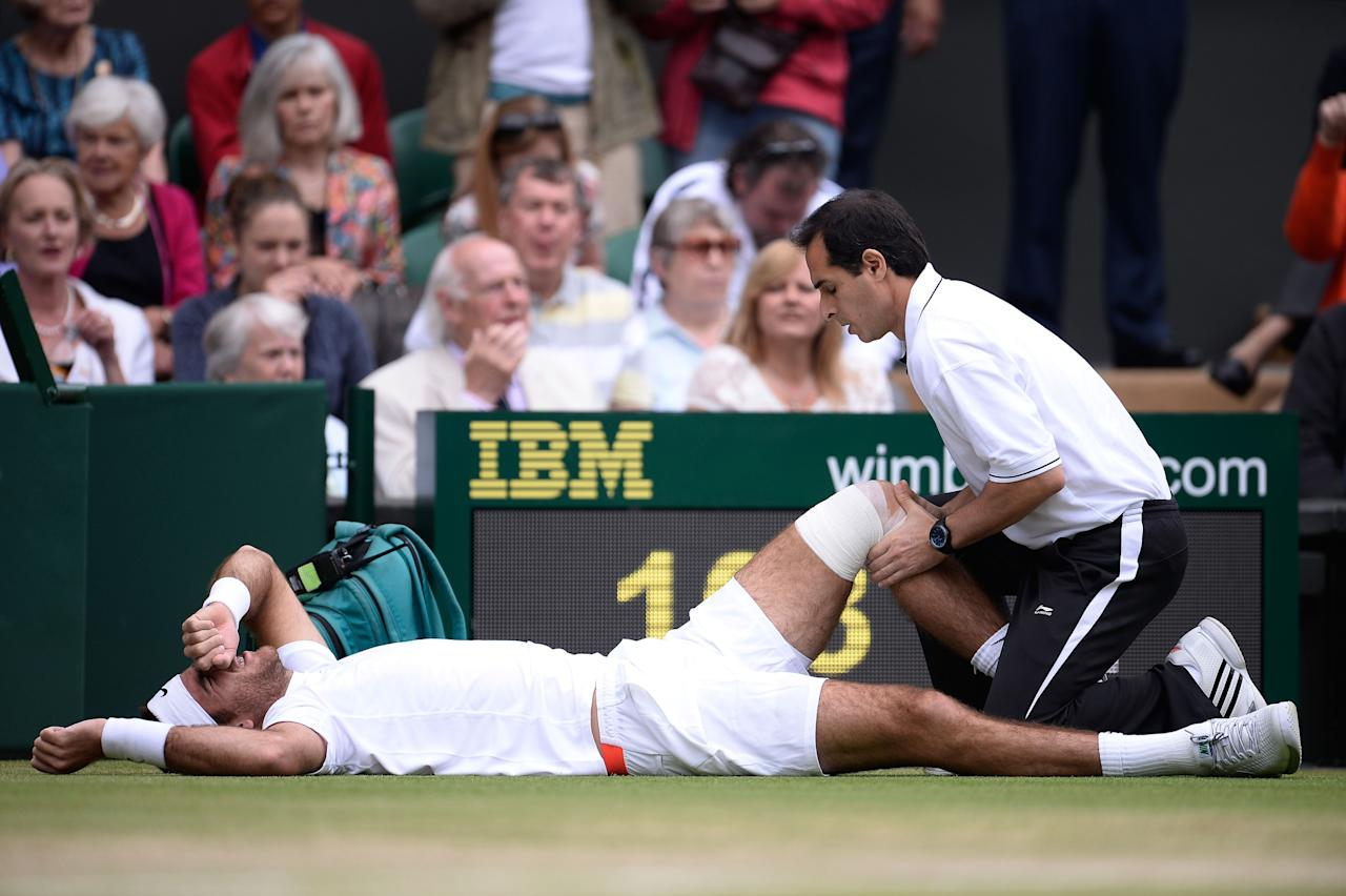 LONDON, ENGLAND - JULY 03: Juan Martin Del Potro of Argentina grimaces as he receives treatment after slipping on the grass during the Gentlemen's Singles quarter-final match against David Ferrer of Spain on day nine of the Wimbledon Lawn Tennis Championships at the All England Lawn Tennis and Croquet Club at Wimbledon on July 3, 2013 in London, England. (Photo by Dennis Grombkowski/Getty Images)