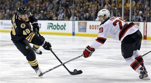 Boston Bruins center Rich Peverley (49) shoots as New Jersey Devils defenseman Mark Fayne (29) tries to block during the second period of an NHL hockey game in Boston, Tuesday, Jan. 29, 2013. (AP Photo/Charles Krupa)