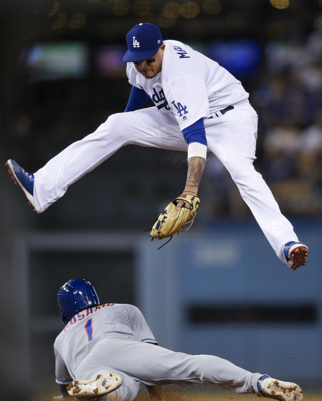 New York Mets shortstop Amed Rosario, bottom, steals second base ahead of the tag by Los Angeles Dodgers shortstop Manny Machado during the ninth inning of a baseball game in Los Angeles, Monday, Sept. 3, 2018. The Mets won 4-2. (AP Photo/Kelvin Kuo)