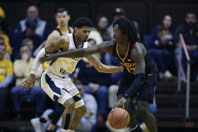 Oklahoma State guard Isaac Likekele (13) drives up court while defended by West Virginia guard James Bolden (3) during the second half of an NCAA college basketball game Saturday, Jan. 12, 2019, in Morgantown, W.Va. (AP Photo/Raymond Thompson)