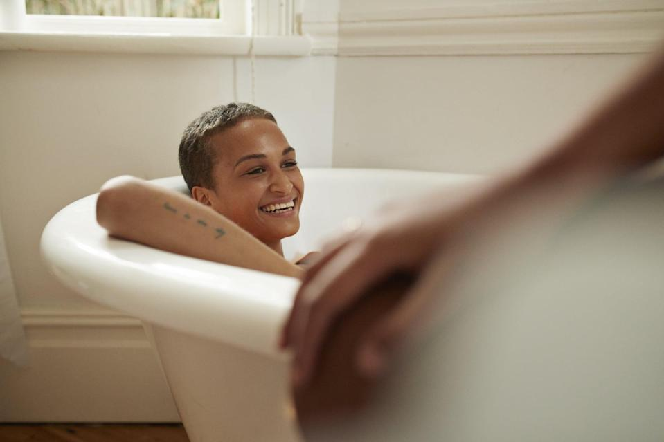 Smiling young woman relaxing in bathtub with female friend at home