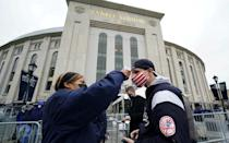Fans have their temperature checked in front of Yankee Stadium in New York on April 1, 2021