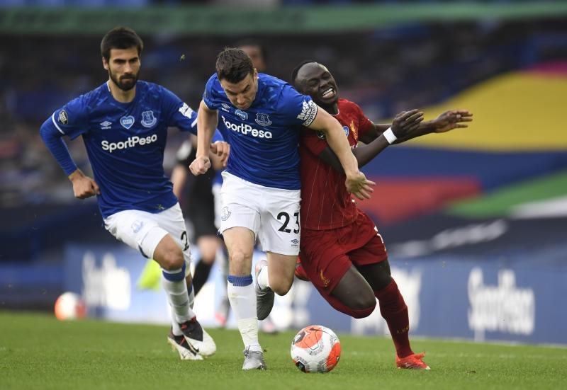 Everton's Seamus Coleman, left, challenges Liverpool's Sadio Mane during the English Premier League soccer match between Everton and Liverpool at Goodison Park in Liverpool, England, Sunday, June 21, 2020. (Peter Powell/Pool via AP)