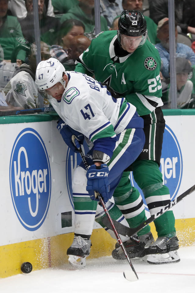 Vancouver Canucks left wing Sven Baertschi (47) and Dallas Stars defenseman Esa Lindell (23) compete for control of the puck in the second period of an NHL hockey game in Dallas, Tuesday, Nov. 19, 2019. (AP Photo/Tony Gutierrez)