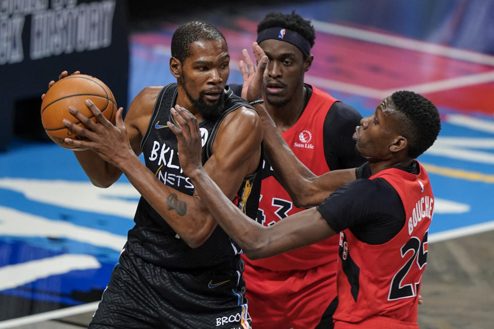 Toronto Raptors' Pascal Siakam (43) and Chris Boucher (25) defend against Brooklyn Nets' Kevin Durant (7) during the first half of an NBA basketball game Friday, Feb. 5, 2021, in New York. (AP Photo/Frank Franklin II)