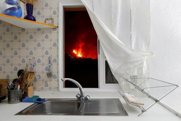 Lava is seen through the window of a kitchen from El Paso following a volcanic eruption on the Canary Island of La Palma, Spain,  on Tuesday (Photo: Reuters)