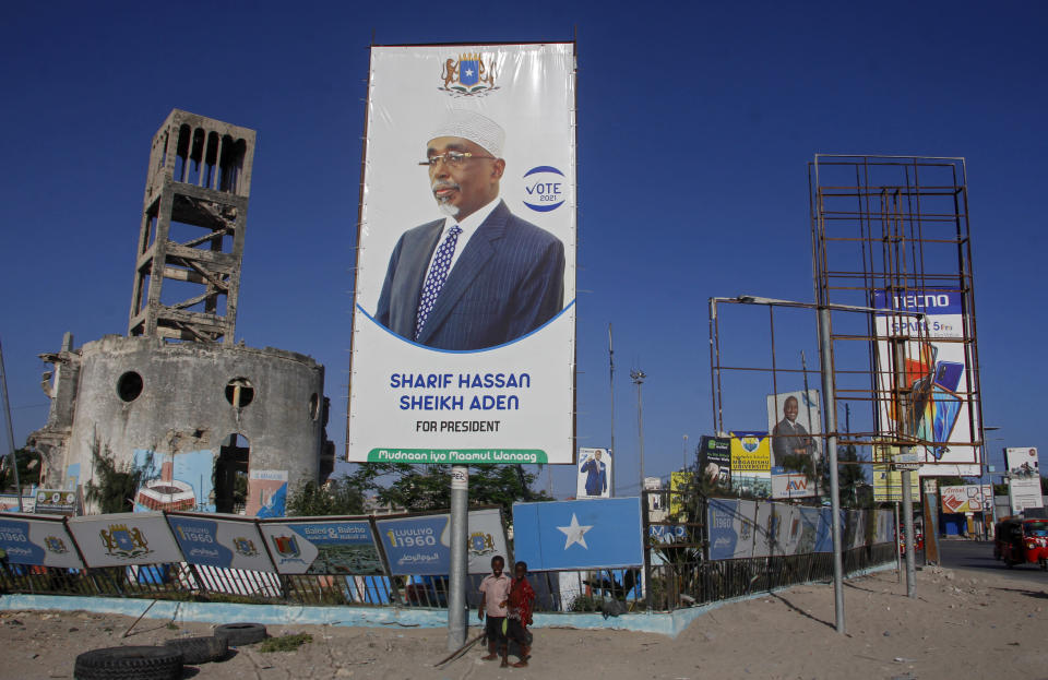 Somali children walk past a billboard showing presidential candidate Sharif Hassan Sheikh Aden in Mogadishu, Somalia Thursday, Jan. 28, 2021. As Somalia marks three decades since a dictator fell and chaos engulfed the country, the government is set to hold a troubled national election but two regional states are refusing to take part in the vote to elect Somalia's president and time is running out before the Feb. 8 date on which mandates expire. (AP Photo/Farah Abdi Warsameh)