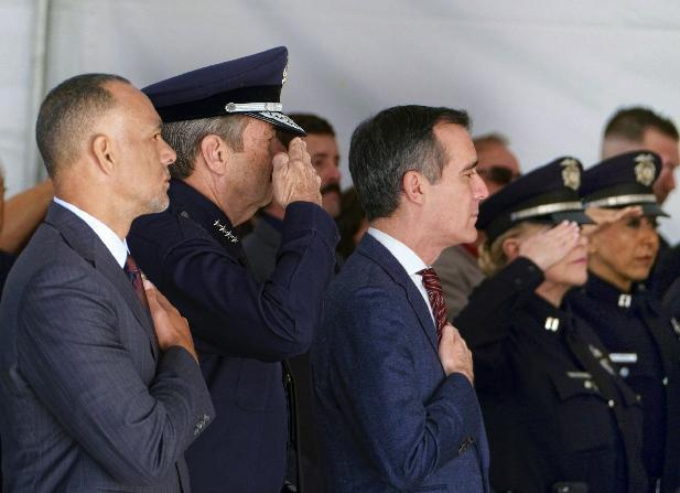 From left to right, Matt Johnson, President of the Los Angeles Police Commission, is joined by LAPD Police Chief Charlie Beck and Los Angeles Mayor Eric Garretti during a ceremony marking the 20th anniversary of an infamous gunbattle between police and two heavily armed bank robbers in Los Angeles on Tuesday, Feb. 28, 2017. The gathering Tuesday morning honored the officers involved in the February 1997 shootout that changed the way police departments nationwide arm officers. (AP Photo/Richard Vogel)