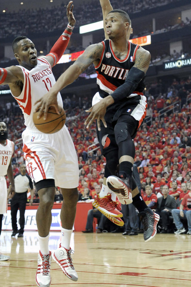Portland Trail Blazers' Damian Lillard, right, looks to pass the ball around Houston Rockets' Dwight Howard (12) in the first half of Game 5 of an opening-round NBA basketball playoff series Wednesday, April 30, 2014, in Houston. (AP Photo/Pat Sullivan)