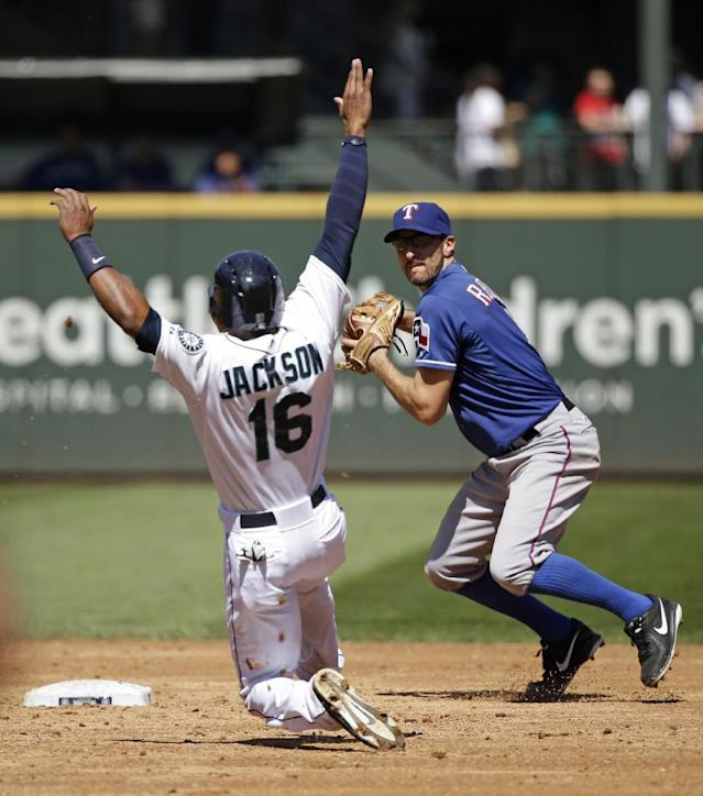 Texas Rangers shortstop Adam Rosales, right takes aim at first base after forcing out Seattle Mariners' Austin Jackson (16) at second base in the third inning of a baseball game Wednesday, Aug. 27, 2014, in Seattle. Rosales completed the double play on Dustin Ackley at first base. (AP Photo/Elaine Thompson)