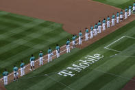 Seattle Mariners left fielder Dee Gordon (9), center, raises his fist during the singing of the national anthem before the Mariners' home opener baseball game against the Oakland Athletics, Friday, July 31, 2020, in Seattle at T-Mobile Park. (AP Photo/Ted S. Warren)