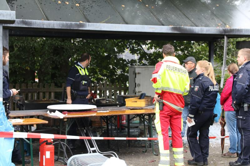 In this Sunday, Sept. 8, 2019 photo police officers investigate a booth after an explosion at a village festival in Freudenberg, Germany. Authorities say 14 people have been injured, five of them with life-threatening burns, during an explosion at a village festival in western Germany. Police told German news agency dpa that it appears likely that oil inside a big frying pan caused the explosion at the local 'Backesfest' (bakery festival) that was attended by about 100 people. (Berthold Stamm/dpa via AP)