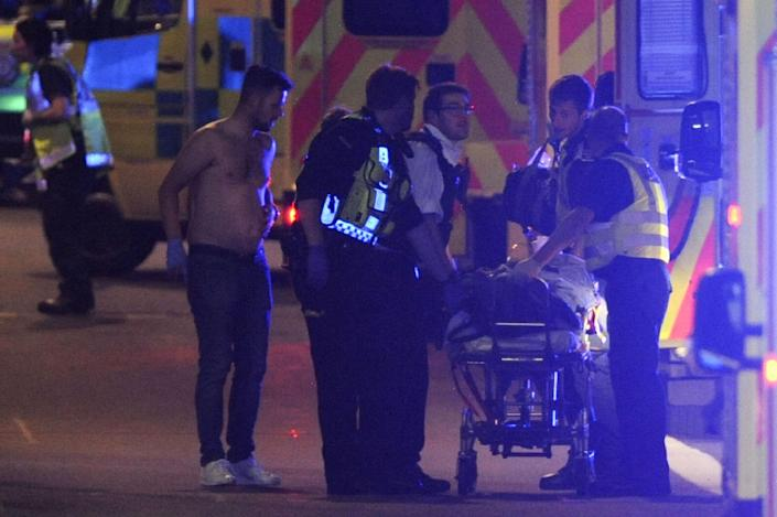 <p>Police officers and members of the emergency services attend to a person injured at the scene of an apparent terror attack on London Bridge in central London on June 3, 2017.<br> Armed police fired shots after reports of stabbings and a van hitting pedestrians on London Bridge on Saturday in an incident reminiscent of a terror attack in March just days ahead of a general election. (Daniel Sorabji/AFP/Getty Images) </p>