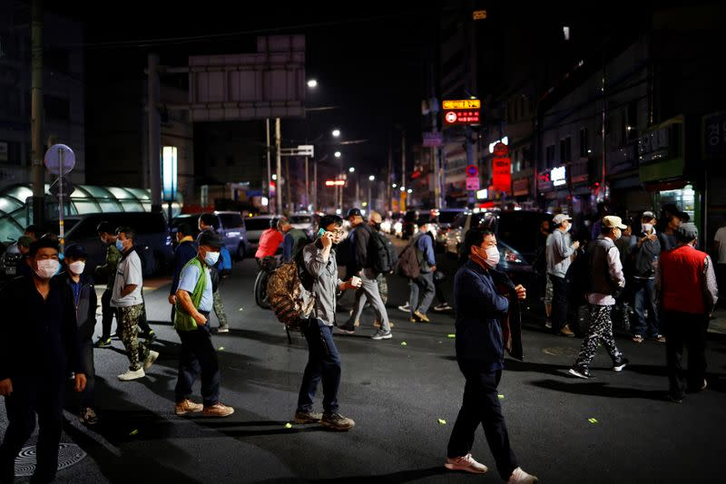 Day workers cross a road as they gather to seek for a job amid the coronavirus disease (COVID-19) pandemic in Seoul