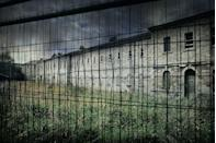 <p>Storm clouds roll over the fenced-off remains of a once-bustling hospital. </p>