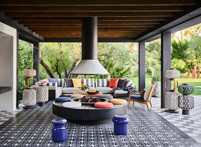 """One of the home's most coveted spaces is this outdoor living room, a festive space outfitted with a sectional sofa from Holly Hunt, a """"Kay"""" low-back lounge chair from <a href=""""https://www.gloster.com"""" rel=""""nofollow noopener"""" target=""""_blank"""" data-ylk=""""slk:Gloster"""" class=""""link rapid-noclick-resp"""">Gloster</a>, and a series of totem-like lanterns designed by Stephen Burks. The huge freestanding fireplace was modeled after the one seen at the Parker, a boutique hotel in Palm Springs."""
