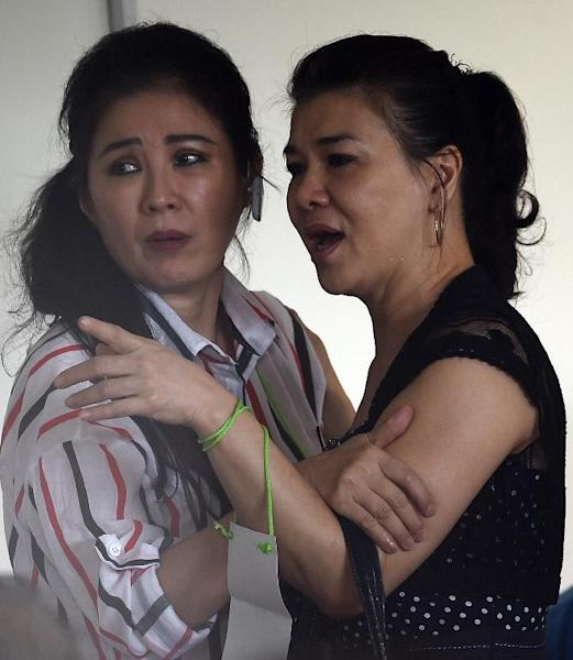 Relatives of passengers onboard the missing AirAsia flight QZ8501 react to news of floating debris spotted in the search for the plane, as they wait at a crisis-centre set up at Juanda International Airport in Surabaya, on December 30, 2014