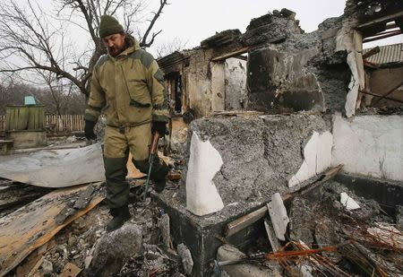 A member of a rebel unit of the self-proclaimed separatist Donetsk People's Republic walks past a house destroyed by shelling in the village of Olenivka, south of Donetsk, February 7, 2015. REUTERS/Maxim Shemetov