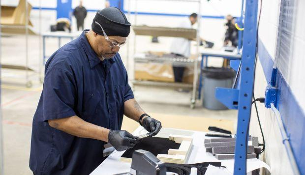 Operators and assemblers assemble medical face shields at Ford Motor Company