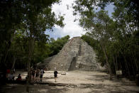 In this Aug. 1, 2018 photo, tourists climb the pyramid at the archeological site of Coba on Mexico's Yucatan Peninsula. Mexico's president-elect Andres Manuel Lopez Obrador wants to bring tourism revenues to more remote and forgotten stretches of Mexico, like Coba, with a train running from Cancun to Palenque, Chiapas. (AP Photo/Eduardo Verdugo)