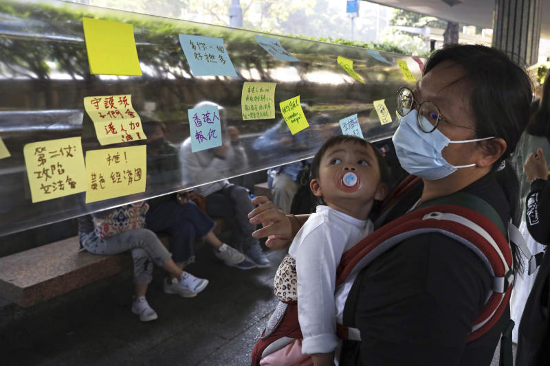 A woman holds a child as she looks at notes on a Lennon wall during a rally for students and elderly pro-democracy demonstrators in Hong Kong, Saturday, Nov. 30, 2019. Hundreds of Hong Kong pro-democracy activists rallied Friday outside the British Consulate, urging the city's former colonial ruler to emulate the U.S. and take concrete actions to support their cause, as police ended a blockade of a university campus after 12 days. (AP Photo/Ng Han Guan)