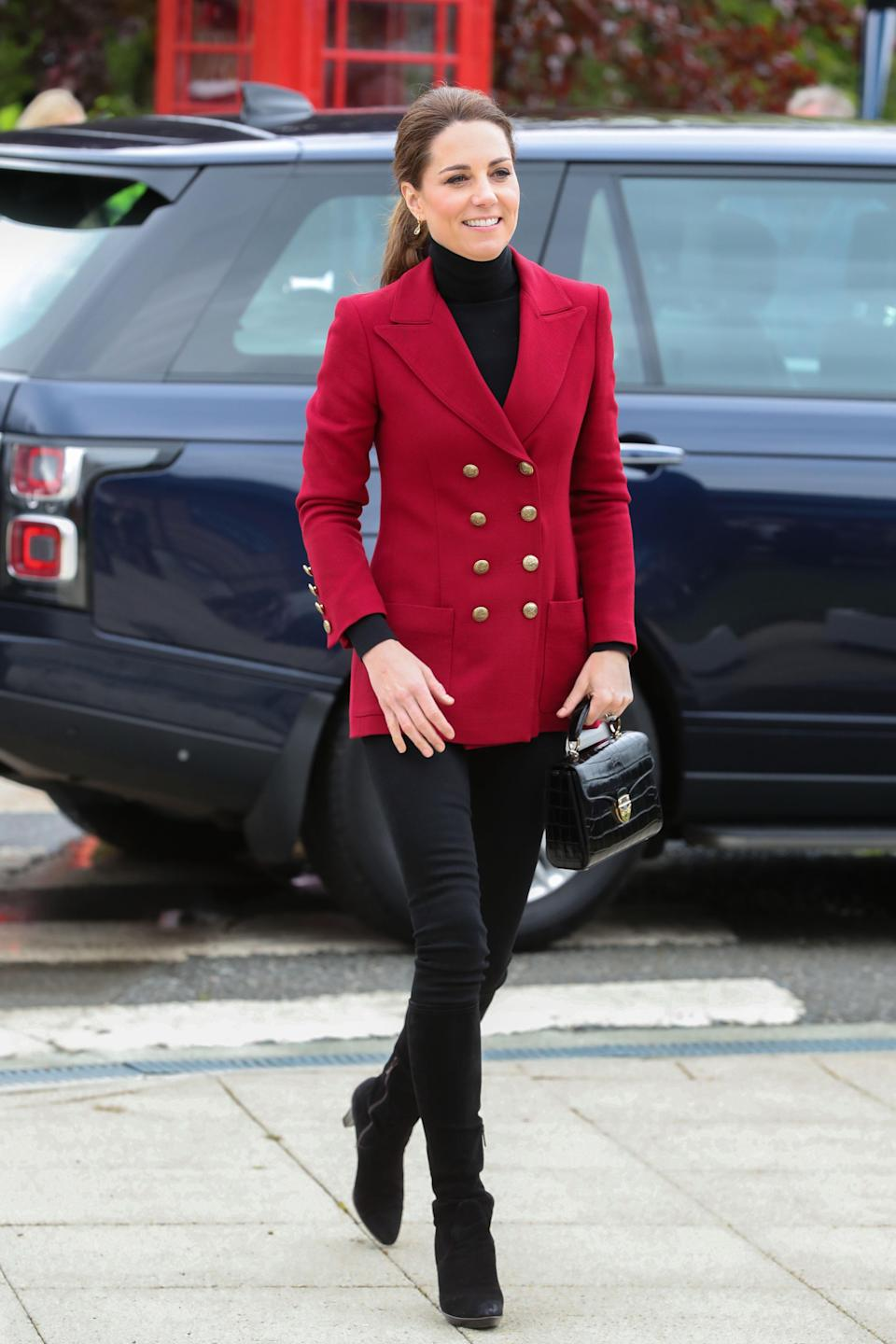 For a day of engagements in North Wales, Kate wore some old fashion favourites. She teamed her red Philosophy by Lorenzo Serafini blazer with a black roll neck and skinny jeans. She accessorised with her Aquatalia 'Rhumba' platform boots, her Aspinal Midi Mayfair bag and her Kiki McDonough citrine drop earrings. [Photo: Getty]